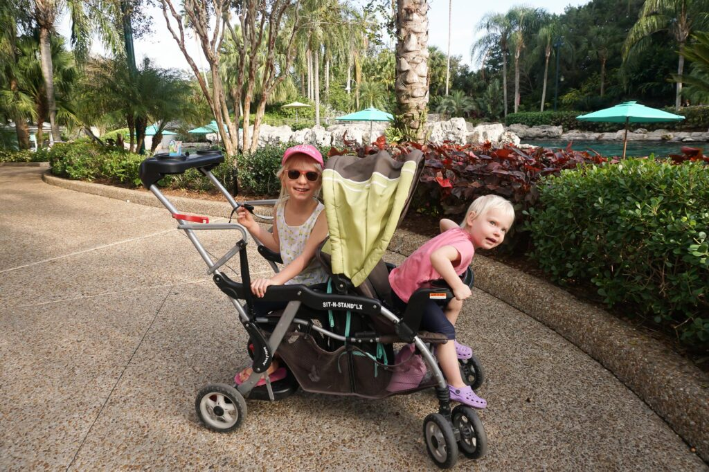 two girls in double stroller sitting back to back in seaworld