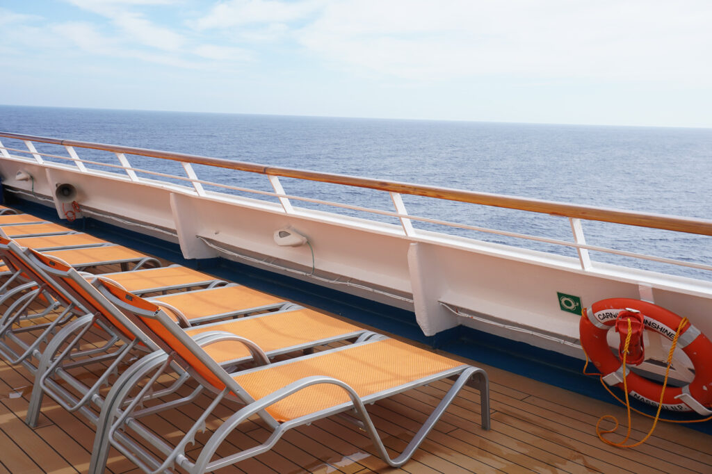 row of orange lounge chairs on cruise ship with view of ocean