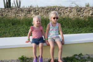 two young girls sitting on low wall in aruba