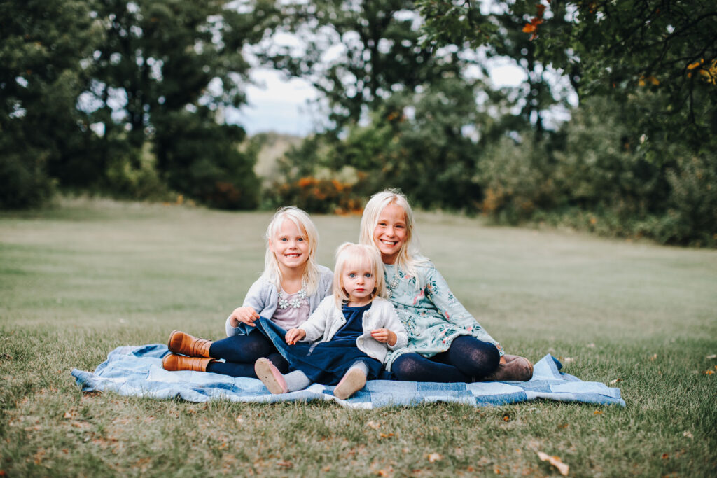 three blond girls sitting on a denim blanket on the grass