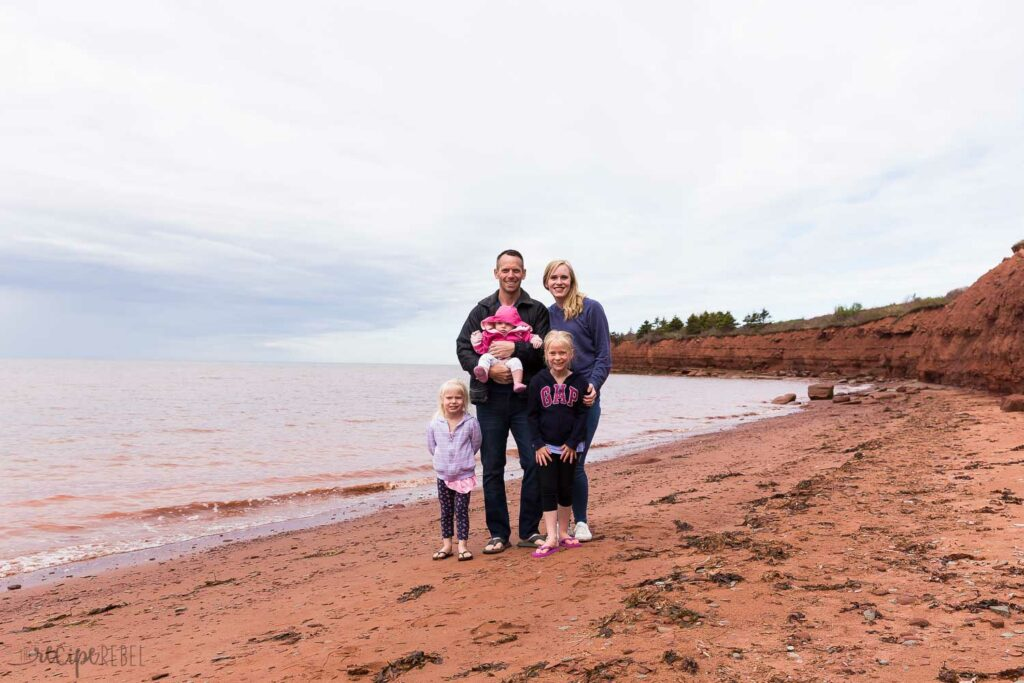 family photo on red sand beach in Prince Edward Island