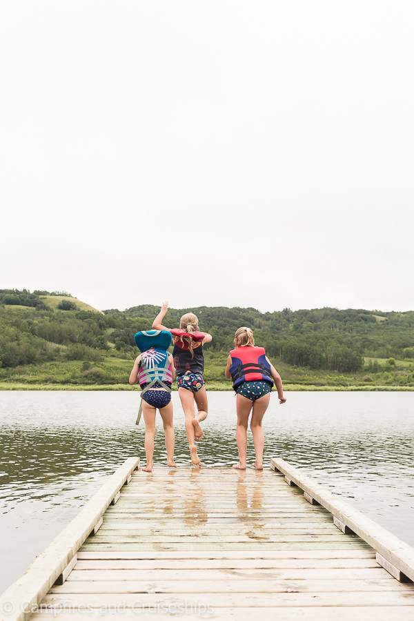 three girls jumping off the dock at asessippi lake manitoba