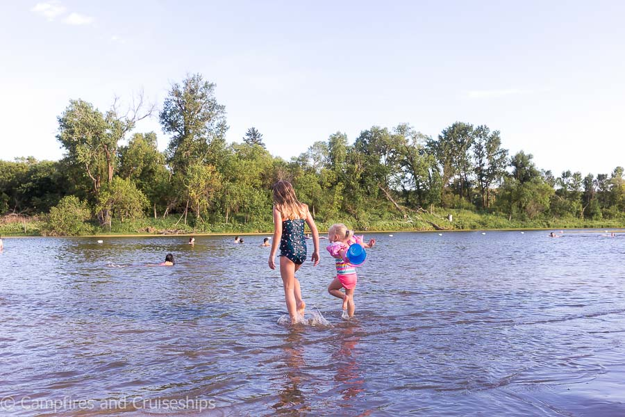 two girls walking in the water at kiche manitou beach