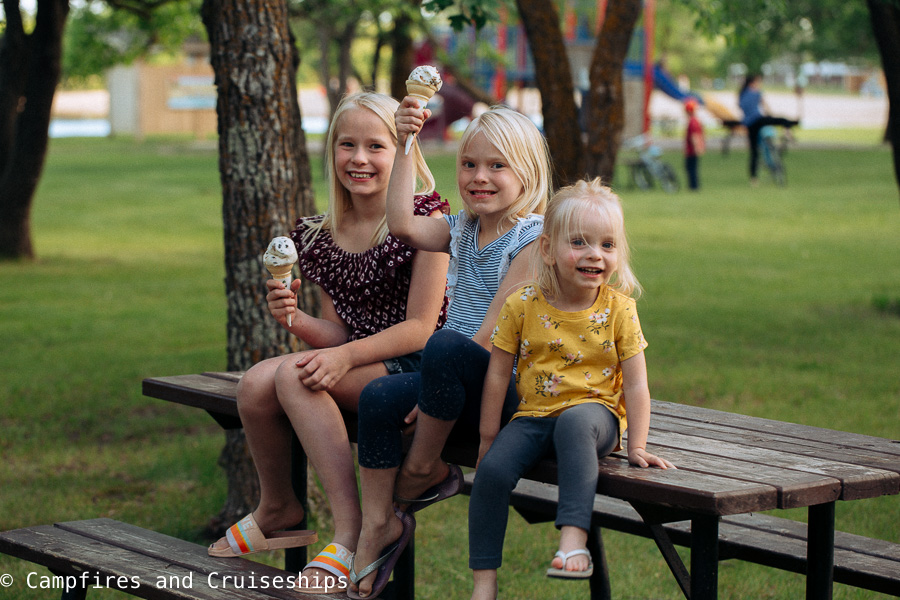 three girls eating ice cream sitting on a picnic table