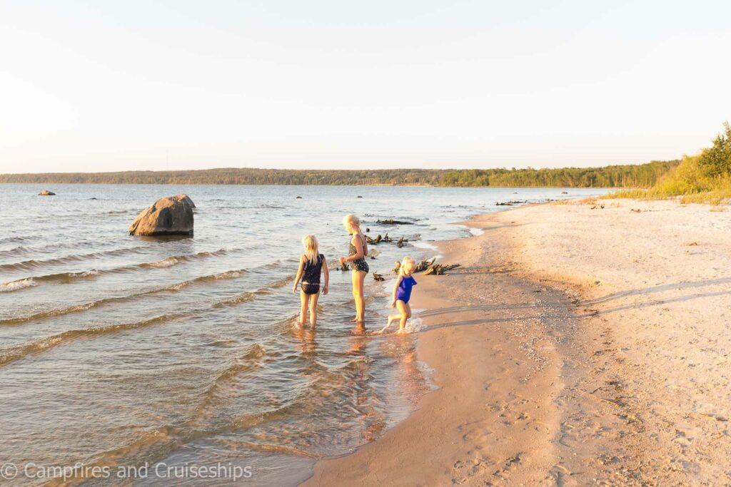 three kids playing on grand beach manitoba