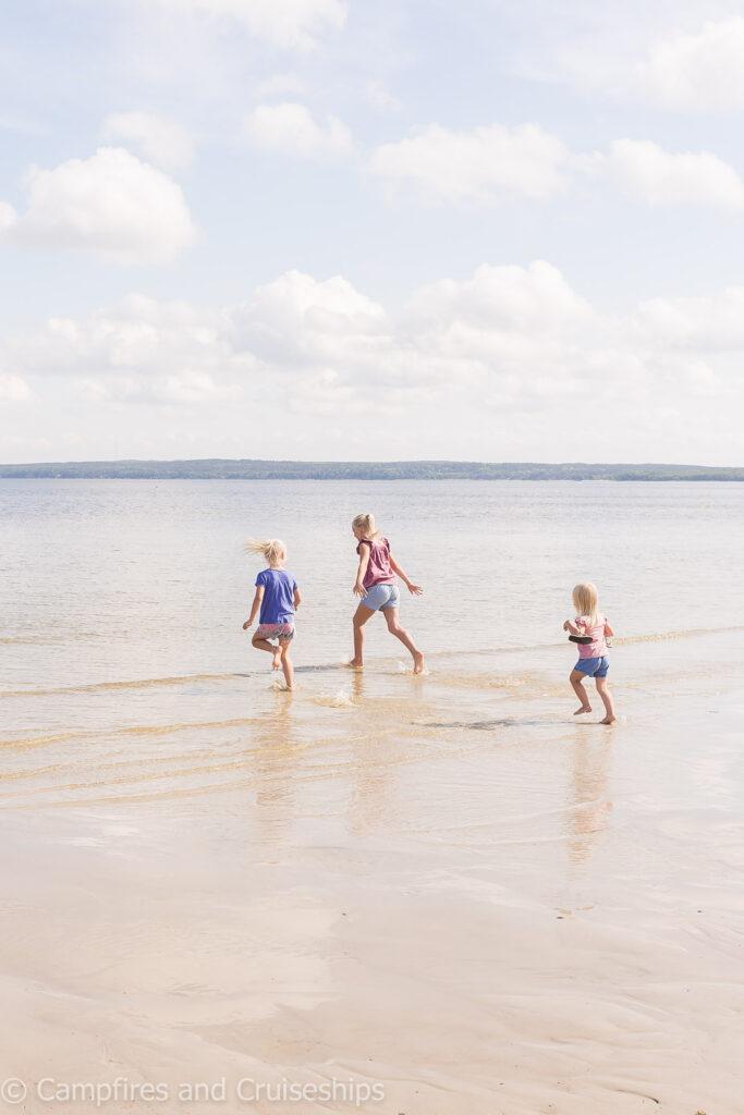 three girls running on grand beach manitoba west beach