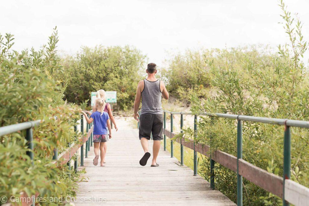 foot bridge at grand beach provincial park three girls and dad