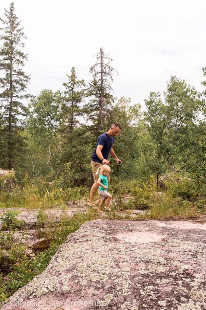 father and daughter walking on the rocks in whiteshell provincial park